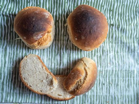 Freshly baked sliced bread on the table smiling face symbol. Top view.