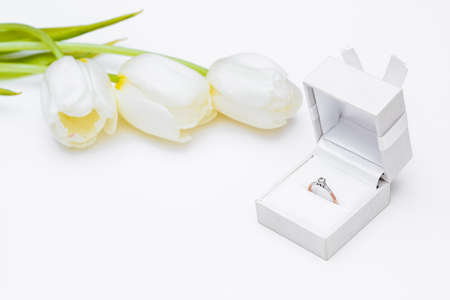tulip and gold engagement ring on a white background photo