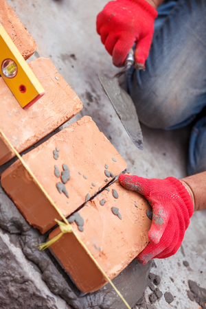 Bricklayer with brick at a construction site Stock Photo