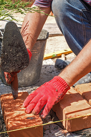 Bricklayer with brick at a construction site photo