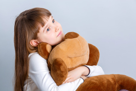 Ein Porträt einer jungen hübschen Mädchen lächelt und umarmt ihren Teddybären