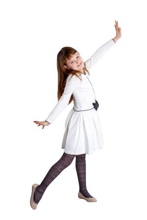 白い背景に白いドレスに立って身に着けているかわいい女の子