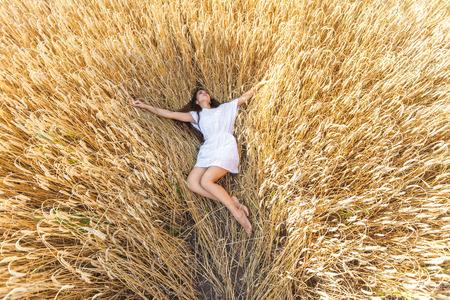 Young  woman in white dress in wheat field. girl in wheat field photo