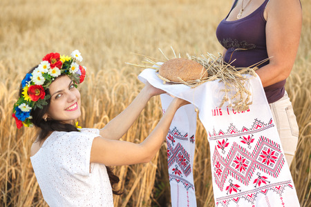 Young  woman in white dress in wheat field hold bread. girl in wheat field photo