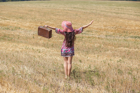 Happy girl in hat on wheat field. Big hat and blowing long hair photo