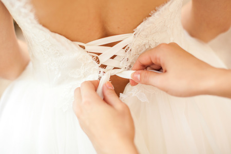 satin dress: Bridesmaid is helping the bride to dress Stock Photo