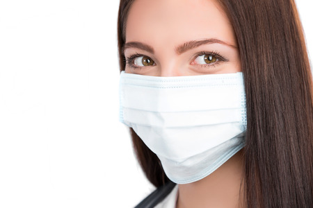 A close-up portrait of a pretty female doctor or nurse with stethoscope wearing a surgical mask  isolated on a white background 스톡 콘텐츠