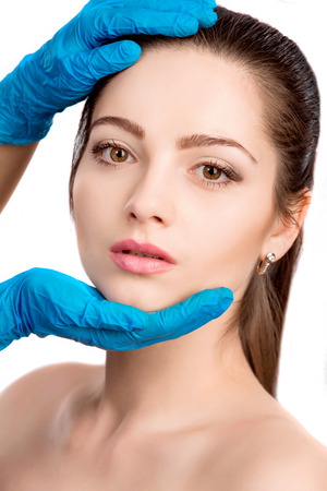 beauty surgery: Female model face with beauty treatment isolated on white  Plastic surgery touching the beautiful woman face. skin check before plastic surgery