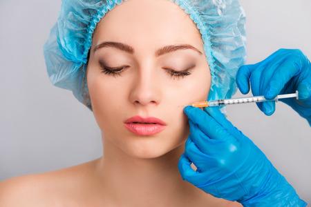 salon beauty: Joven hermosa joven que recibe una inyecci�n de botox cosm�tico en su cara, de cerca