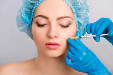 beauty treatment clinic: Young beautiful  woman receiving a cosmetic botox injection in her face, close up