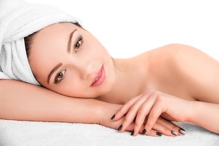 toallas: Joven y bella mujer atractiva recibiendo tratamiento de masaje y spa facial sobre fondo blanco. Piel Perfecta. Protección De La Piel. Piel joven Foto de archivo