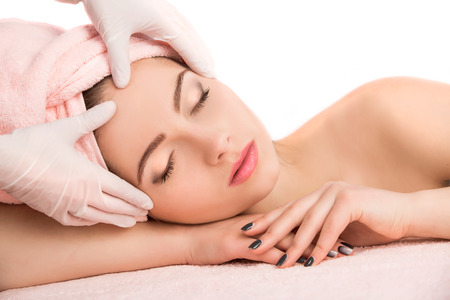 limpieza de cutis: Joven y bella mujer atractiva recibiendo tratamiento de masaje y spa facial sobre fondo blanco. Piel Perfecta. Protección De La Piel. Piel joven Foto de archivo