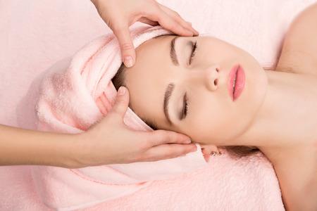 toallas: Hermosa joven atractiva mujer de recibir el masaje facial y tratamiento de spa. Piel Perfecta. Protección De La Piel. Piel joven
