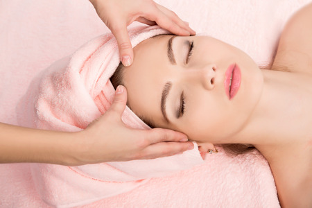 alternative wellness: Young beautiful  attractive woman receiving facial massage and spa treatment. Perfect Skin. Skincare. Young Skin