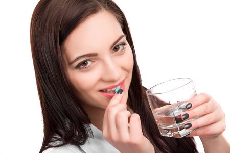 若い魅力的な女性医師水を飲んで頭痛手を取る薬薬錠剤、白い背景で隔離のガラス 写真素材