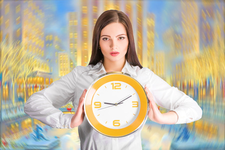 punctual: Portrait of beautiful young business woman holding in hands clock, discipline and punctual concept