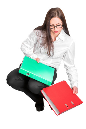 dropped: Portrait of attractive businesswoman in glasses dropped red and green folders isolated on white background
