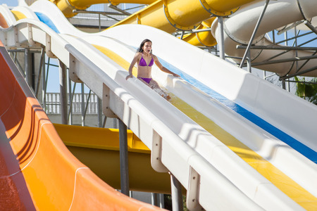water park: Happy  girl in bikini sliding water park. Stock Photo