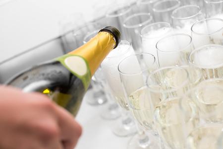 ウェイターがグラスにシャンパンを注ぐ