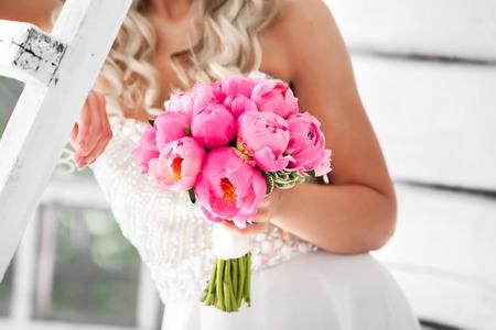 ピンクのシャクヤクのウェディング ブーケを持って花嫁