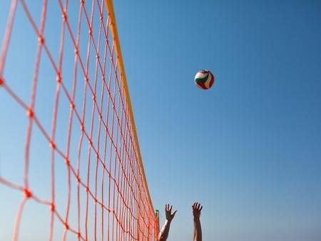 voleibol: Voleibol peligro en Net En El Fondo Del Cielo Azul soleado de verano. Bola de vuelo a través del aire en la playa