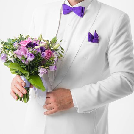 white suit: the groom in a white suit holding a wedding bouquet