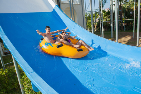 water activity: Couple cheering while having fun sliding down a water slide at public swimming pool