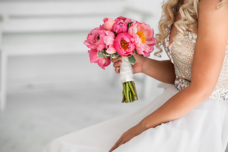 peony: bride holding beautiful wedding bouquet of pink peonies Stock Photo