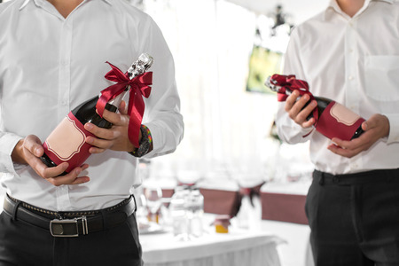 excelsior: the waiter holds a bottle of champagne