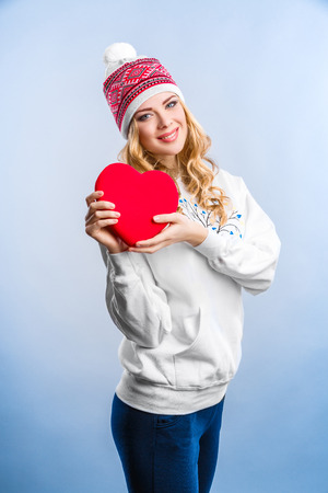 sweatshirt: smiling blonde woman in a white sweatshirt holding a red heart. Valentines day