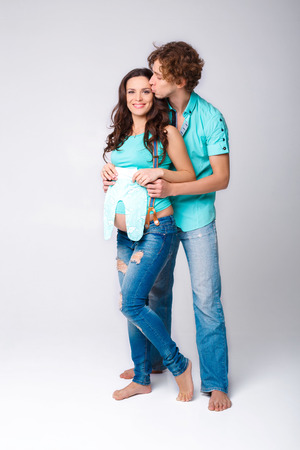 pregnant jeans: beautiful pregnant woman with her husband holding sliders. future mother and father in blue t-shirt and jeans