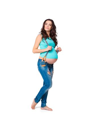 pregnant jeans: beautiful brunette pregnant woman. attractive mom in the blue t-shirt and jeans Stock Photo