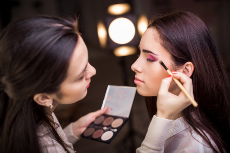 Make-up-Künstler anwenden Make-up zu einem Modell.
