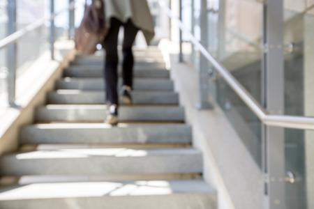 계단 배경을 흐리게. 여자 다리가 계단을 오르다.