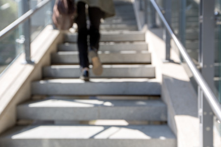 go up: blur stairs background. womens legs go up the stairs