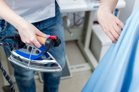 snipping: Tailor ironing the fabric. seamstress irons dress in a sewing workshop Stock Photo