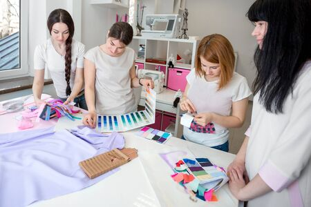 designer clothes: tailors choose the fabric for the dress. Sketches of clothes and fabric samples on the sewing table. the designer is working Stock Photo