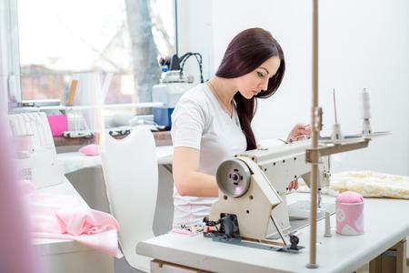 Schöne Frau Näherin an der Nähmaschine Kleider nähen. Nähwerkstatt Standard-Bild - 55810644