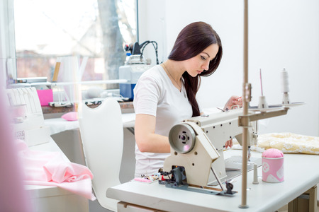 schöne Frau Näherin an der Nähmaschine Kleider nähen. Nähwerkstatt Lizenzfreie Bilder