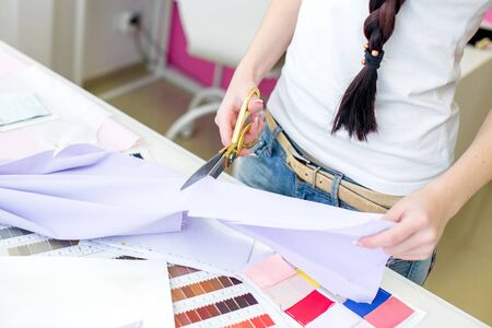 designer clothes: the seamstress cuts fabric with scissors. Sketches of clothes and fabric samples on the table. the designer is working