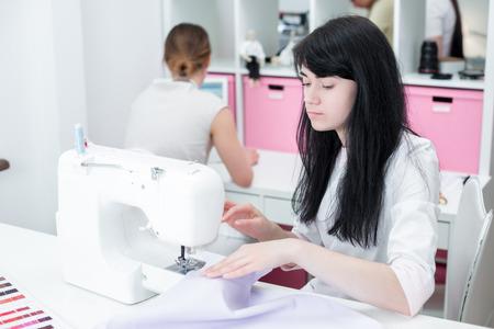 mooie vrouw naai naaister op de naaimachine kleren. naai-atelier