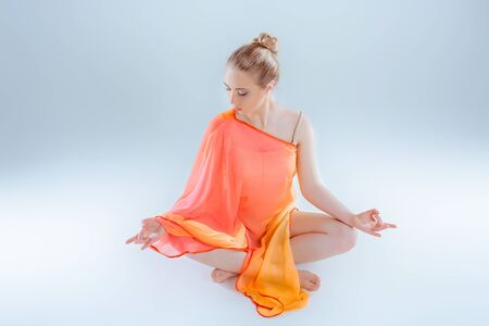 Young woman in orange dress practicing yoga, sitting in Lotus position