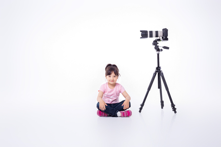 floor standing: little cute girl sitting on the floor, standing next to the modern professional photo camera on tripod. child photographs Stock Photo