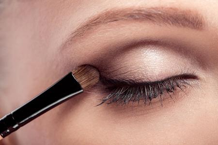 ojos marrones: artista de maquillaje se ocupa pincel de maquillaje para los ojos. maquillaje para una hermosa joven. sombra de ojos marrón. de cerca