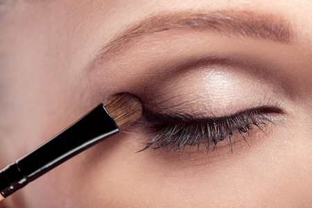 makeup artist deals makeup brush for eyes. makeup for a young beautiful girl. brown eye shadow. close up 免版税图像