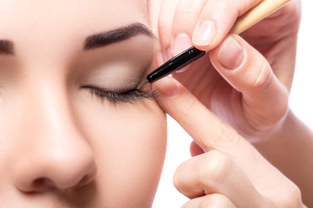makeup artist deals makeup brush for eyes. makeup for a young beautiful girl. brown eye shadow. Stock Photo
