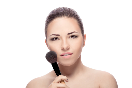 makeover: Beauty woman with Makeup Brushes. Natural Make-up for Brunette girl with Brown Eyes. Beautiful Face. Makeover. Perfect Skin. Applying Makeup Stock Photo