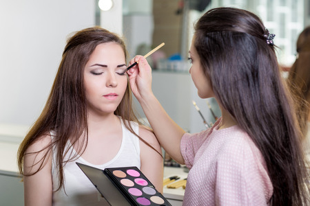 make-up artist doing professional make up of young charming woman 스톡 콘텐츠