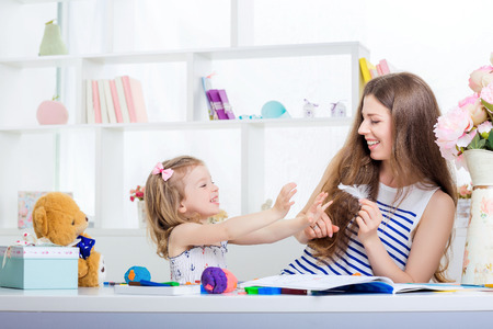 chuckle: beautiful young mother  tickles her little daughter. mother and daughter having fun at home.