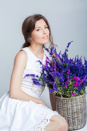 arm bouquet: beautiful young woman holding a basket of lavender Stock Photo